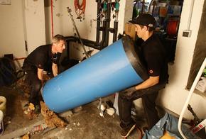 Handwerker tragen den alten Speicher aus dem Keller.