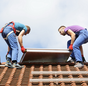 Installation Solarthermie: Männer heben einen Kollektor aufs Dach