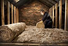 Dacharbeiten für die Wärmedämmung. Ein Handwerker mit Mundschutz rollt Dämmmatten aus.