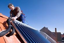 Handwerker mit Kollektor für Solarthermie auf Dach