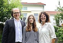 Familienfoto: dreiköpfige Familie Kucharzik im Garten, Haus mit Solarthermie im Hintergrund