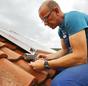 Mann auf Dach schließt Solarkollektor an