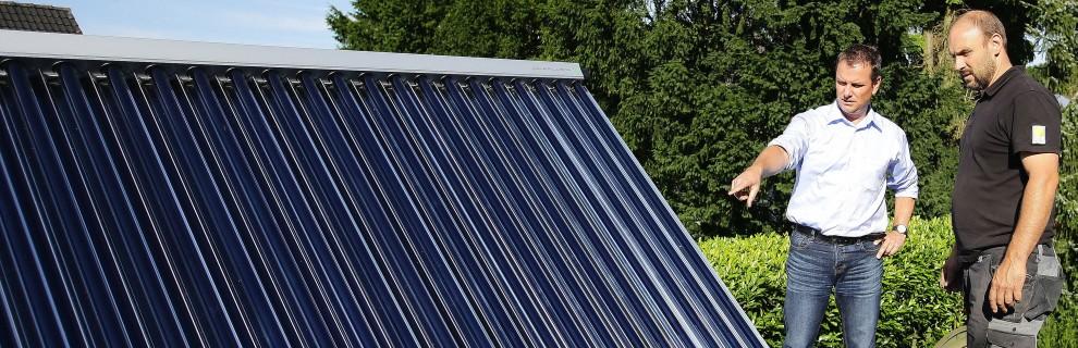 Aufgeständerter Solarthermie-Röhrenkollektor mit Hauseigentümer und Handwerker
